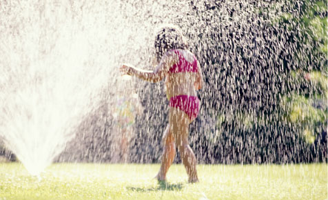 girls under a sprinkler